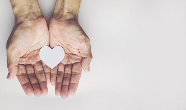 Vieil homme mains tenant en forme de cœur sur fond blanc. assurance maladie ou concept de l'amour
