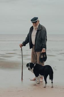 Vieil homme marchant avec son chien sur une plage au lever du soleil