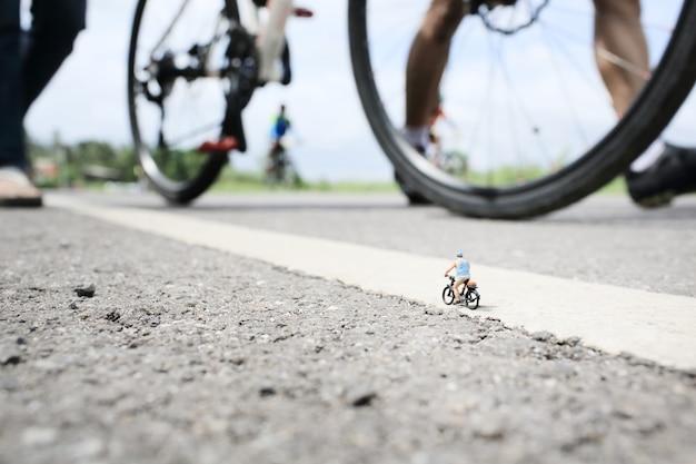 Un vieil homme miniature sur balade à vélo en route de campagne avec un groupe de fond de course cycliste