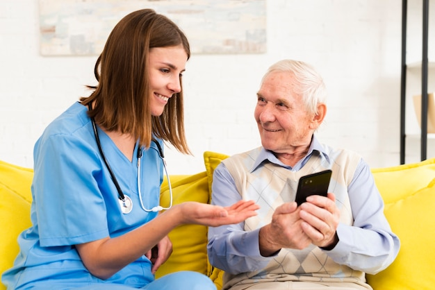 Vieil homme montrant des photos sur le téléphone au soignant