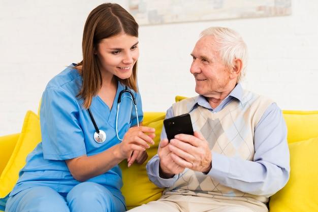 Vieil homme montrant des photos sur le téléphone à l'infirmière
