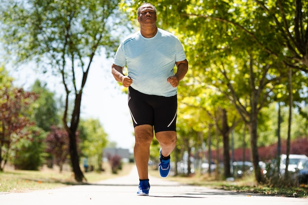 Un vieil homme noir court dans le parc et fait de gros efforts pour réduire le surpoids