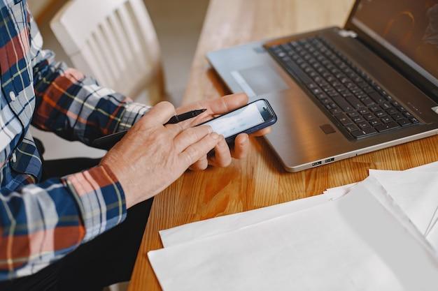 Vieil homme avec ordinateur portable. grand-père assis dans une décoration de noël. homme avec téléphone portable.
