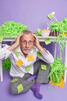 Un vieil homme perplexe et submergé dans des lunettes a beaucoup à faire porte des vêtements domestiques avec des notes collantes rappelant collées garde les mains sur la tête est assis sur le sol près du bureau des piles de papier vert découpé autour