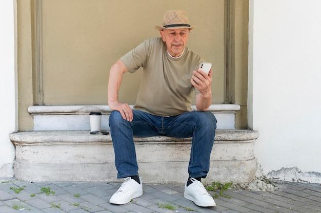 Vieil homme plein coup tenant un smartphone