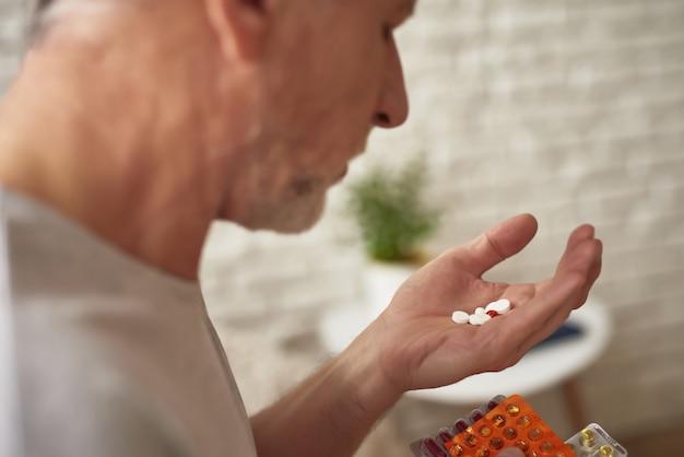 Le vieil homme prend des pilules dans l'aspirine anti-douleur du matin.