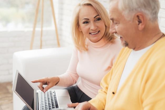 Vieil homme près de vieille femme avec smartphone et ordinateur portable.