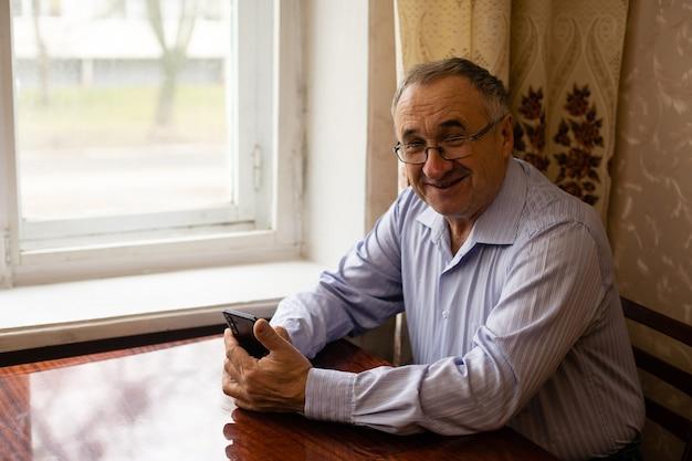 Vieil homme regardant le smartphone pour lire la mise à jour des actualités ou jouer aux applications de réseaux sociaux.