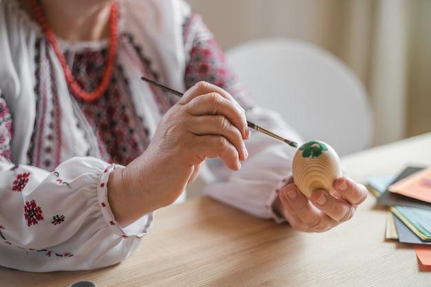 Un vieil homme à la retraite excité a peint un œuf de pâques. oeufs de pâques bricolage