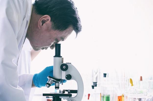 Vieil homme scientifique à l'aide de microscope en laboratoire