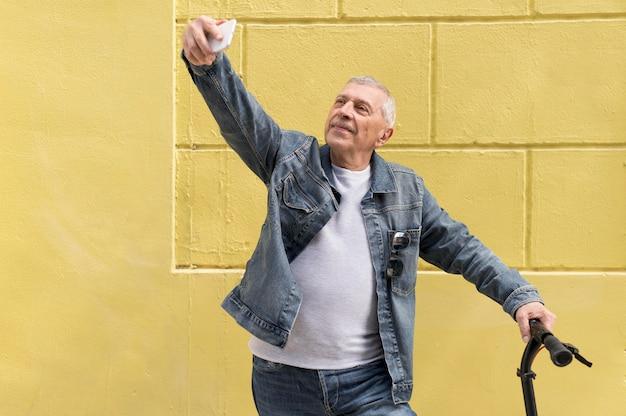 Vieil homme avec scooter prenant selfie