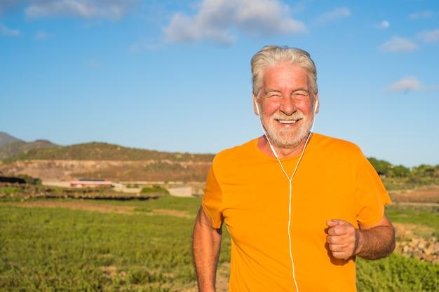 Vieil homme ou senior courant seul dans une zone rurale autour de la nature et des maisons - un homme mûr faisant de l'exercice et perdant du poids