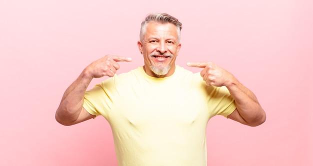 Vieil homme senior souriant pointant avec confiance vers son propre large sourire, attitude positive, détendue et satisfaite