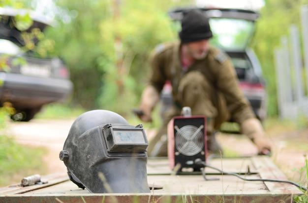 Vieil homme soudeur en uniforme brun prépare la surface de la porte en métal pour le soudage avec une machine de soudage à l'arc à l'extérieur