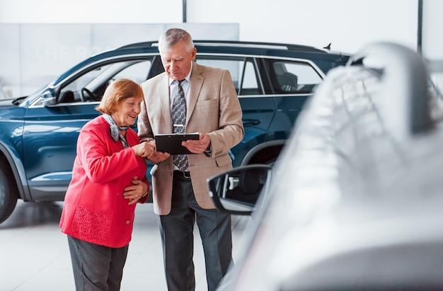 Vieil homme en tenue de soirée avec bloc-notes soutenant la femme dans le choix de l'automobile.