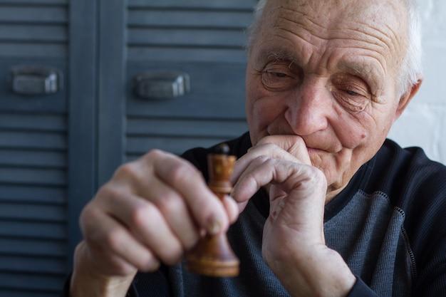 Le vieil homme tient dans ses mains la pièce d'échecs du roi