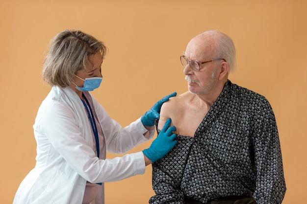Un vieil homme de tir moyen après un vaccin