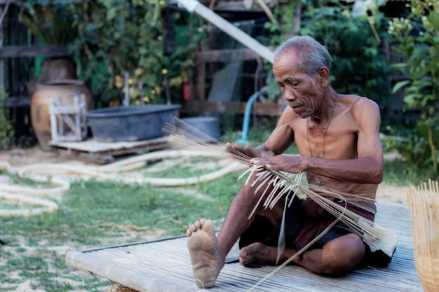 Un vieil homme tisse dans la campagne thaïlandaise.