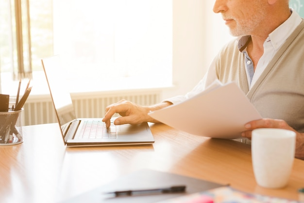 Vieil homme travaillant sur un ordinateur portable