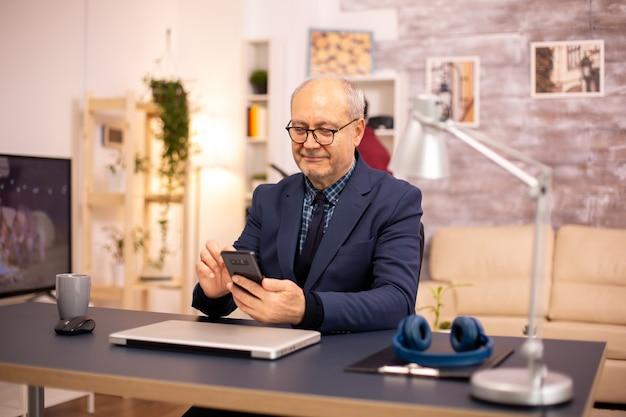 Vieil homme utilisant la nouvelle technologie dans une maison confortable. il a un smartphone dans les mains