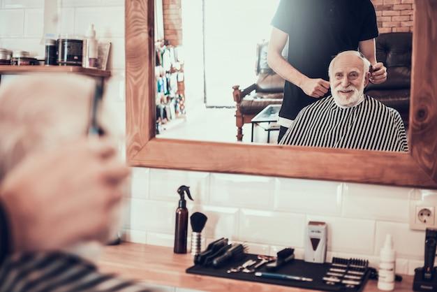 Vieil homme venu au jeune coiffeur pour une coupe de cheveux de style
