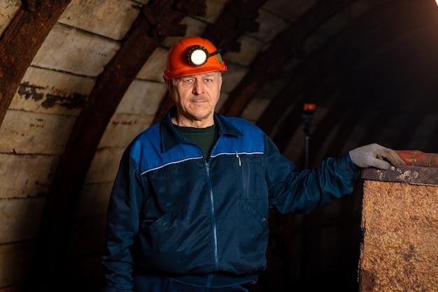 Un vieil homme vêtu d'une combinaison de travail et d'un casque se tient près de la vieille caravane.