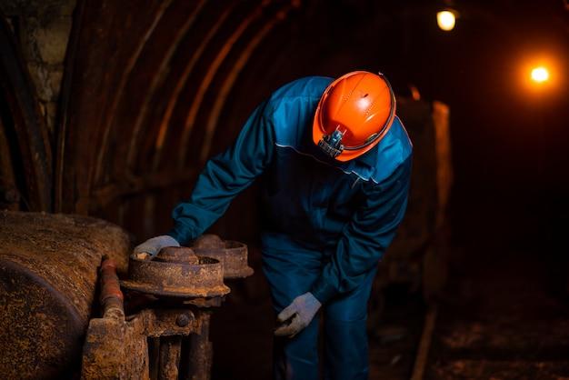 Un vieil homme vêtu d'une combinaison de travail et d'un casque