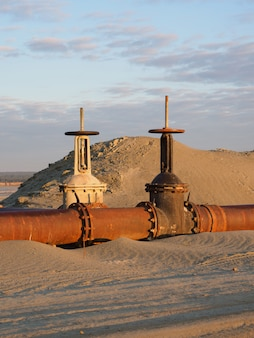 Un vieil oléoduc rouillé dans le désert avec des vannes. pipeline pour le pétrole ou le gaz à l'aube. exploitation des ressources naturelles.