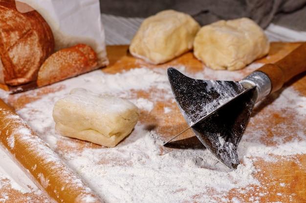 Un vieil outil avec un couteau pour faire de la pâte hachée pour gâteau napoléon sur table en bois
