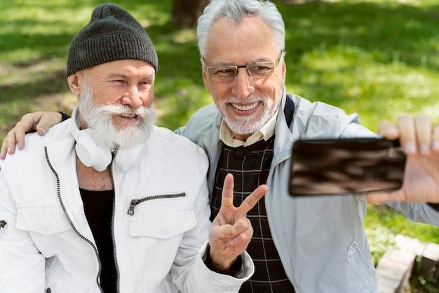 Des vieillards à plan moyen prenant des selfies