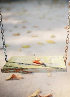 Une vieille balançoire en bois pendue dans le parc, photo aux tons pastel doux.