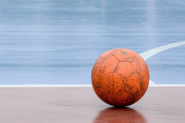Vieille balle orange endommagée à la cour de futsal