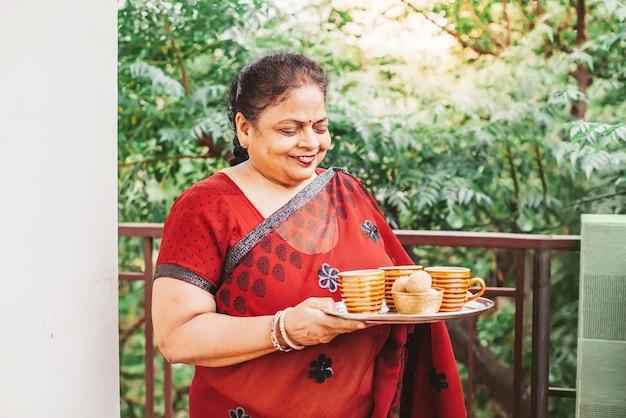 Vieille belle femme indienne tenant un plateau avec du thé