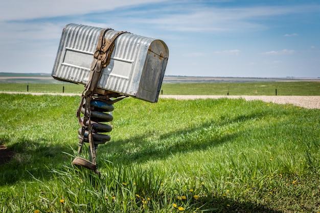 Une vieille boîte aux lettres en métal avec une bride enroulée autour de celle-ci dans une région rurale de la saskatchewan, canada