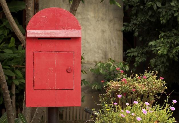 Vieille boîte aux lettres rouge dans le jardin
