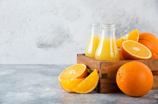 Une vieille boîte en bois pleine de fruits orange et de pichets en verre de jus sur table en pierre.