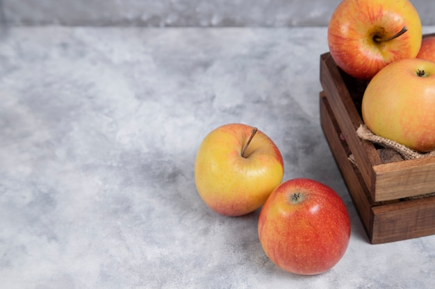 Une vieille boîte en bois pleine de pommes rouges mûres fraîches placées sur un fond de marbre. photo de haute qualité