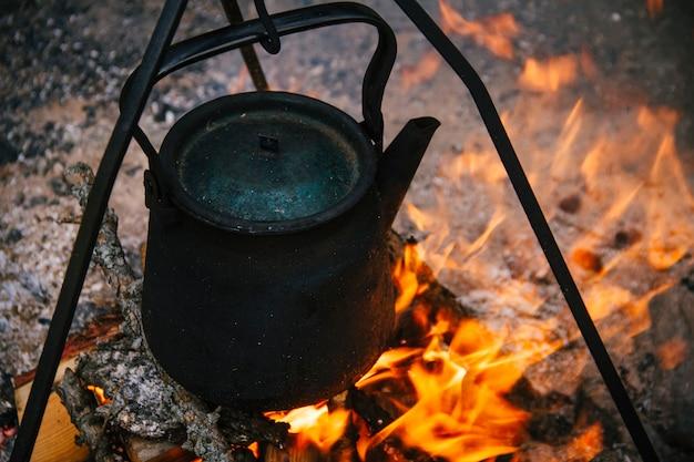 Une vieille bouilloire brûle, des touristes font bouillir de l'eau