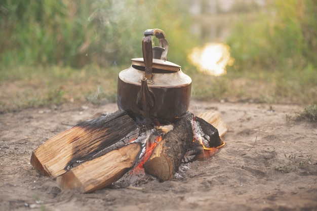 Vieille bouilloire en fer sur bois brûlant, camping
