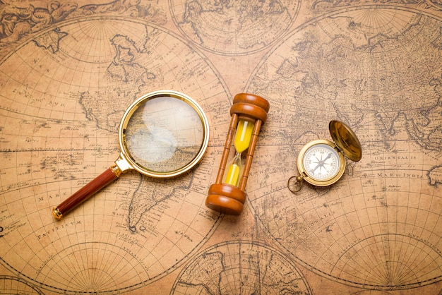 Vieille boussole, loupe et horloge de sable sur la carte vintage