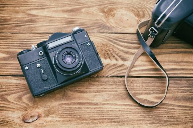 Une vieille caméra sur une table faite de planches texturées sombres.
