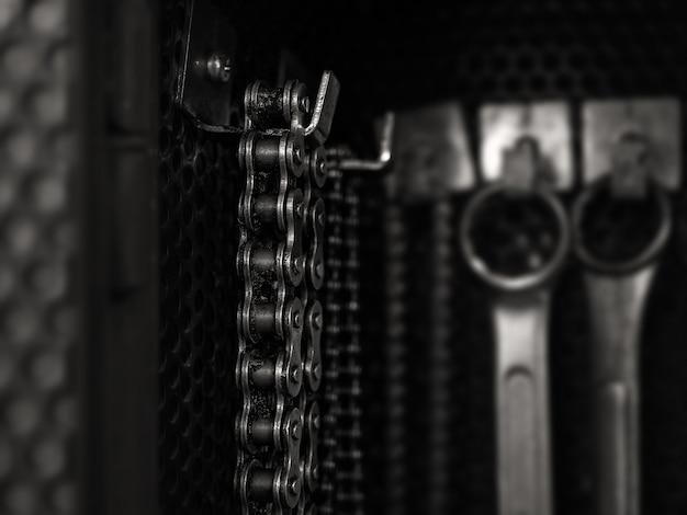 Vieille chaîne sale suspendue à la planche à outils