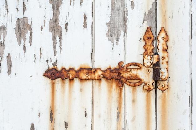 Vieille charnière rouillée sur une porte blanche