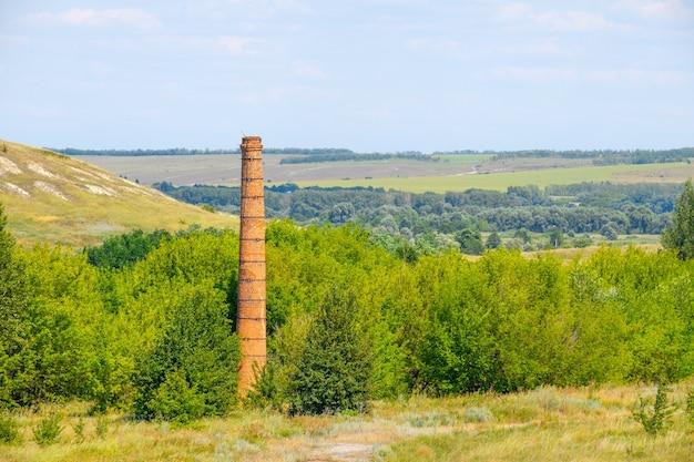 Vieille cheminée en brique abandonnée dans le contexte d'un paysage par une journée d'été ensoleillée