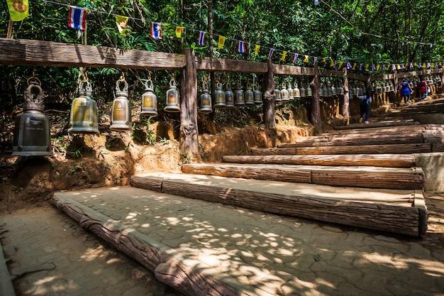 La vieille cloche est suspendue à un rail en acier dans la pierre avec l'empreinte du seigneur bouddha