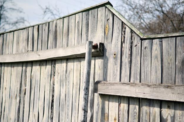 Vieille clôture en bois avec une ferme de campagne, ciel bleu. concept minimal de printemps. fond naturel.
