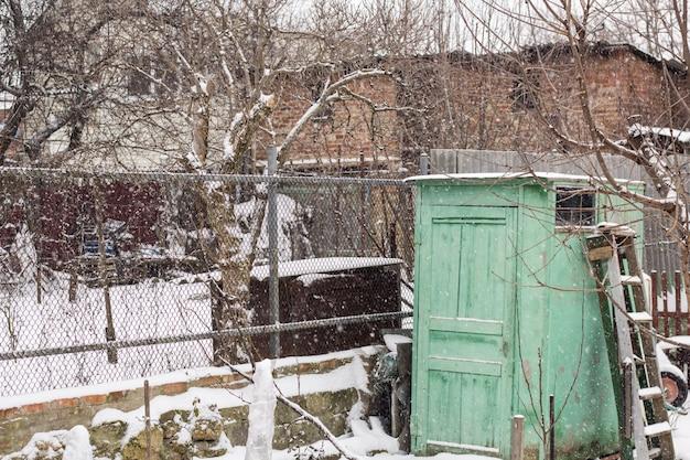 Vieille clôture couverte de neige devant une vieille maison, scène glaciale d'hiver