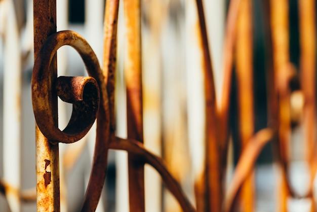 Vieille clôture forgée avec peinture blanche écaillée recouverte de rouille au soleil