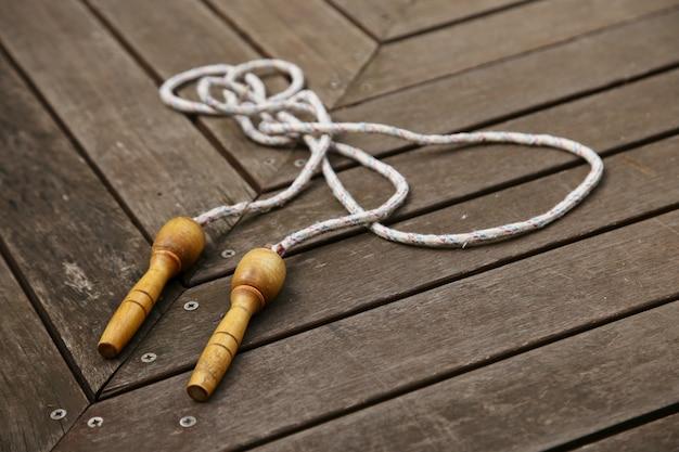 Une vieille corde à sauter sur une terrasse en bois. faire de l'exercice