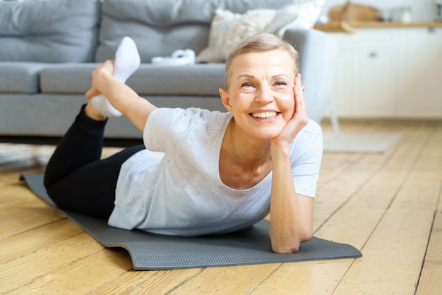 Une vieille dame âgée souriante et souriante étend les mains aux pieds en équilibrant l'exercice de yoga